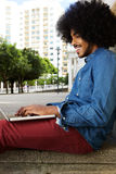 Young guy with afro typing on laptop outside in the city Royalty Free Stock Images