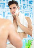 Young guy applying cream to his face for a shave Royalty Free Stock Images
