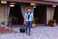 Young Guy Arab Businessman Student Came go to Restaurant With Su. Arabic Muslim Young Man Coming Out of Corner and Goes With Travel Bag to Modern Restaurant Royalty Free Stock Images