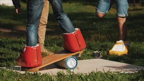 Young guy attempts to balance board on a cylinder while wearing giant boots. Young guy attempts to balance board on a cylinder while wearing giant grotesque red stock video
