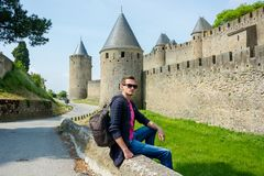 A young guy with backpack sits near fortress wall of the medieval city Carcassonne in France. A young man with backpack sits near fortress wall of the medieval royalty free stock photography