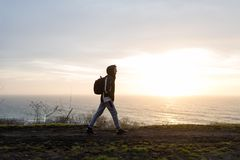 The guy steps along the cliff over the sea. A young guy with a backpack walking along the cliff over the sea during the time of the dawn Royalty Free Stock Photos