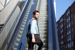 Young guy with bags walking up escalator Royalty Free Stock Image