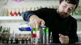 Young guy barman prepares vivid drink and slowly pouring bright scotch from bottle into glass with alcohol on counter on. Unfocused background of bottles stock footage