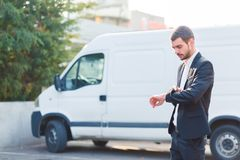 A young guy in a suit looks at the time in the background of the car. Stock Photo