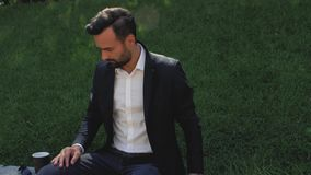 Young guy with a beard in a classic suit sits in a park on a background of grass and drinks coffee from a disposable cup. 4k. 4k. Video stock video footage