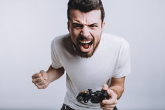 Young guy with beard holding joystick pretending he is playing games Royalty Free Stock Image