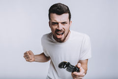 Young guy with beard holding joystick pretending he is playing games. Young attractive guy with beard holding joystick. Serious man is screaming because of Royalty Free Stock Photo