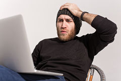 Young guy with a beard with a laptop Royalty Free Stock Image