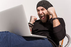 Young guy with a beard with a laptop Royalty Free Stock Photography