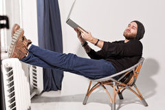 Young guy with a beard with a laptop Royalty Free Stock Photos