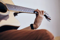 Young guy with a beard on a light background playing the guitar Stock Image