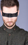A young guy with a beard and a mustache with glasses. The black strip on the eyes. Eyes narrowed. Closeup portrait Stock Photos