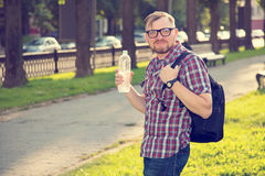 Young guy with a beard and mustache with glasses posing on the street in the sunlight, fashion man, style, vintage style, retro me Royalty Free Stock Images