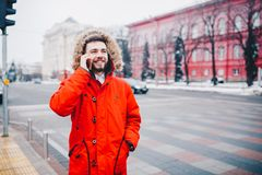 Young guy with beard and red jacket in hood a student uses mobile phone, holds in his hand near the head, talking on the phone wit. H smile on the background of Stock Photography