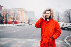 Young guy with beard and red jacket in hood a student uses mobile phone, holds in his hand near the head, talking on the phone wit. H smile on the background of Royalty Free Stock Images