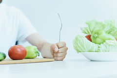 Young guy with beard on white background, vegetables, vegan, healthy eating right stock photography