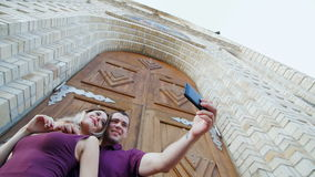 Young guy and beautiful girl doing selfie on the background of the big beautiful doors.  stock footage