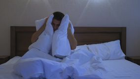 Young guy in bed covering his head and ears with pillow as he does not want to wake up, suffering from noisy alarm in. The morning or sleep disorder, having a stock video footage