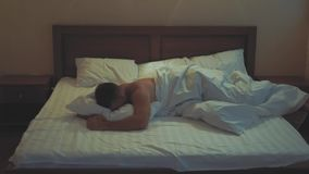 Young guy in bed covering his head and ears with pillow as he does not want to wake up, suffering from noisy alarm in
