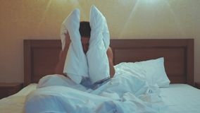 Young guy in bed covering his head and ears with pillow as he does not want to wake up, suffering from noisy alarm in. The morning or sleep disorder, having a stock video