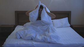 Young guy in bed covering his head and ears with pillow as he does not want to wake up, suffering from noisy alarm in. The morning or sleep disorder, having a stock footage