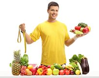 Young guy behind a table with fruit and vegetables holding a mea Stock Photos