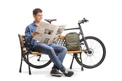 Young guy with a bicycle and a backpack sitting on a wooden benc. H and reading a newspaper isolated on white background Stock Images