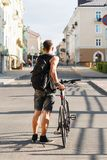 Young guy with a bicycle goes along the street. Travel Royalty Free Stock Photos