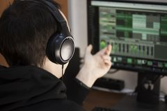 A young guy in big black headphones close-ups at a computer handles music tracks. Create music tracks on the computer. Royalty Free Stock Photography
