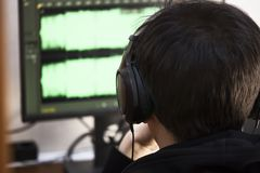 A young guy in big black headphones close-ups at a computer handles music tracks. Create music tracks on the computer. Stock Photos