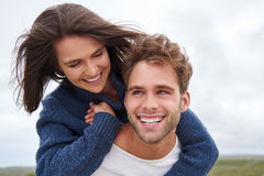 Young guy with a big smile piggybacking his girlfriend. Handsome young guy smiling broadly while looking up and piggybacking his laughing girlfriend Royalty Free Stock Photos