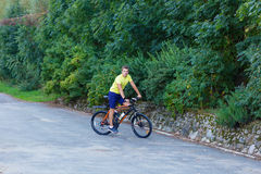 A young guy on a bike outdoors Royalty Free Stock Photos