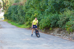 A young guy on a bike outdoors Royalty Free Stock Image