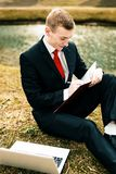 Young guy in a black suit and red tie writes in a notebook. a man works remotely in nature in a park near the river on a. Laptop stock images