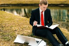 Young guy in a black suit and red tie writes in a notebook. a man works remotely in nature in a park near the river on a. Laptop stock photo