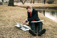 Young guy in a black suit and red tie writes in a notebook. a man works remotely in nature in a park near the river on a. Laptop stock photography