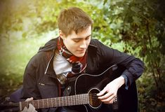 A young guy plays a black acoustic guitar, sitting in the Park. A young guy in a black windbreaker and a plaid scarf plays a black acoustic guitar, sitting in royalty free stock image