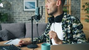 Young guy drinking coffee and talking in microphone making podcast at home. Young guy blogger is drinking coffee and talking in microphone making podcast at home stock footage