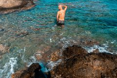 Young guy in a blue Rocky sea stock images