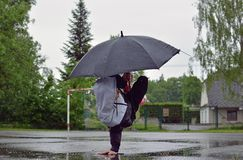 Young guy breakdance dancing in the rain with an umbrella Royalty Free Stock Images