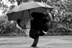Young guy breakdance dancing in the rain with an umbrella Royalty Free Stock Photos