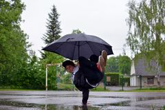 Young guy breakdance dancing in the rain with an umbrella Stock Photos
