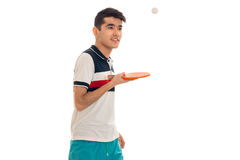 A young guy in a bright t-shirt stands sideways and holding a tennis racket isolated on white background. A young guy in a bright t-shirt stands sideways and stock images