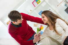 Young guy brings flowers to his girlfriend. Stock Image