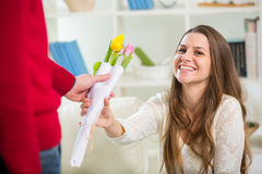 Young guy brings flowers to his girlfriend Stock Images