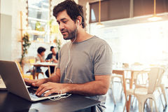 Young guy at a cafe surfing internet on laptop Royalty Free Stock Photos