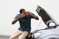 Young guy calls for help with by broken down car Stock Photography