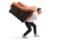 Young guy carrying an armchair on his back stock image