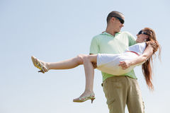 Young Guy Carrying His Girlfriend In His Arms. Outdoor royalty free stock image